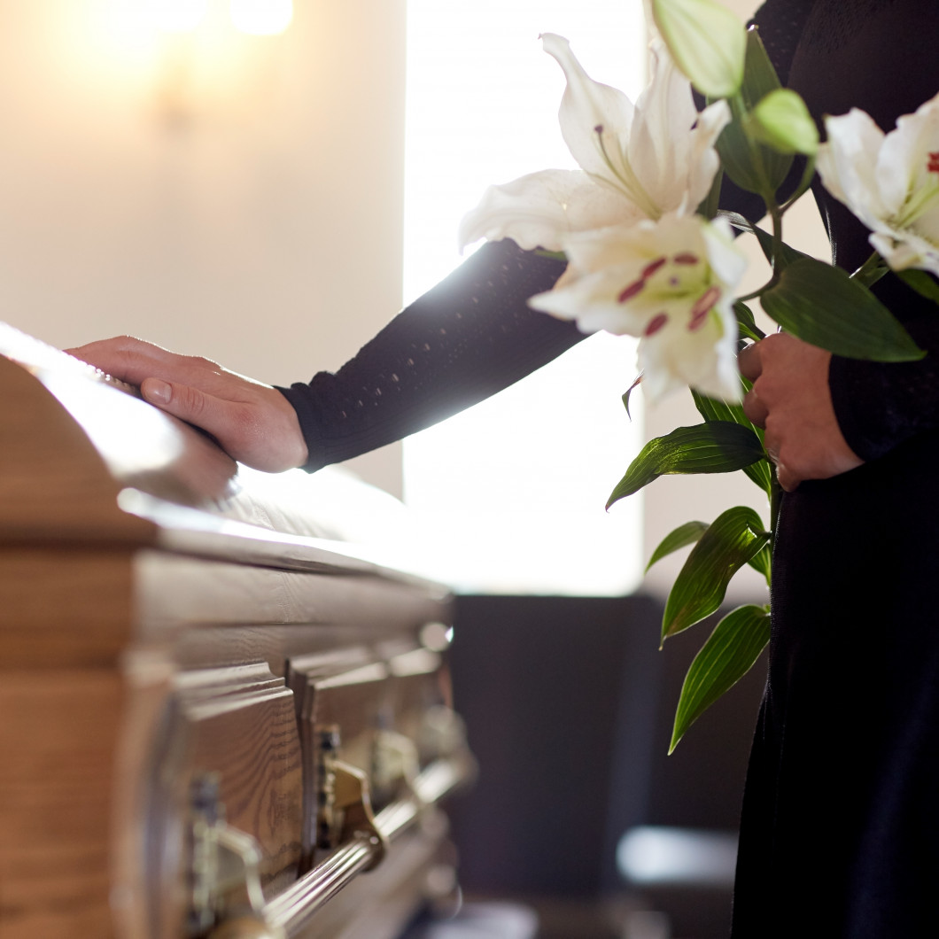 Woman placing her hand on casket while holding flowers