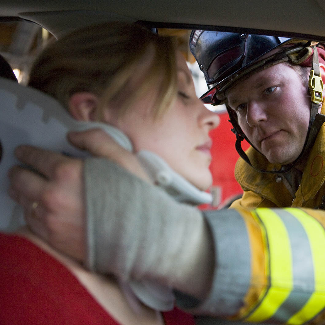 Emergency personnel putting neck brace on woman after car accident